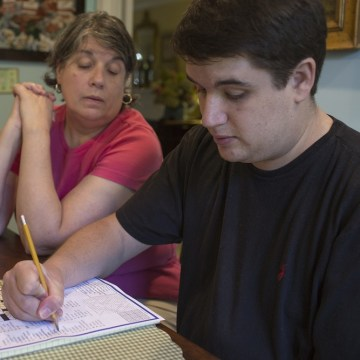 Mac Fedge, 31, does a crossword puzzle while his mother, Kathy Fedge, watches in their Reston, Va. home on Thursday, Sept. 5, 2013.  In September 2001...