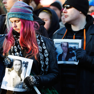 People hold photographs of 17-year-old Rehtaeh Parsons during a memorial vigil at Victoria Park in Halifax, Nova Scotia April 11, 2013. Parsons died o...