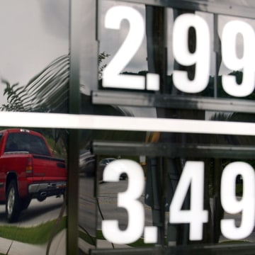 In this Monday, July 1, 2013,  photo, vehicles are reflected in a sign advertising unleaded gas for $2.99 at a QuikTrip station at the corner of Woodr...