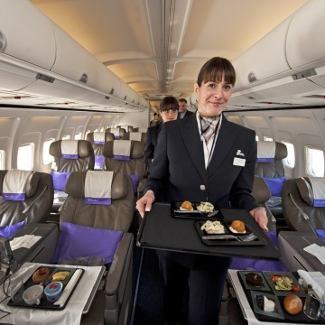 A flight attendant for the new airline Open Skies, a 100 percent business class airline with authentic French cuisine, poses on March 24, 2010 at Wash...