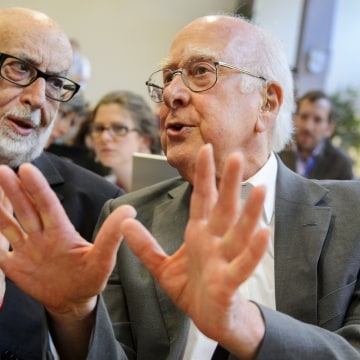 (FILES) This file picture dated July 4, 2012 shows British physicist Peter Higgs (R) speaking with Belgium physicist Francois Englert at a press confe...
