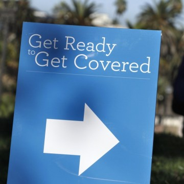 A man is silhouetted behind a sign at an Affordable Care Act outreach event hosted by Planned Parenthood for the Latino community in Los Angeles, Cali...
