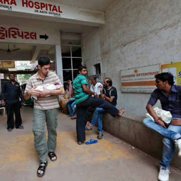 Daniele Fabbricatore, 39, from Britain, carries his week-old-baby girl Gabriella, after she was discharged from the Akanksha IVF centre in Anand town,...