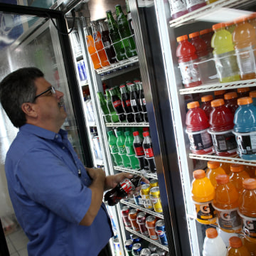 MIAMI, FL - DECEMBER 09:  Gilberto Flores stocks the shelf with Diet Coke at the Amerika convience store on December 9, 2013 in Miami, Florida. Accord...