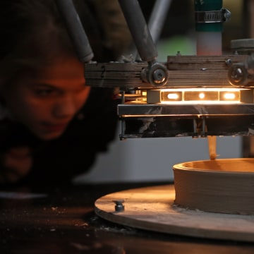 A visitor watches as a 3-D printer builds a bee house using liquefied clay.