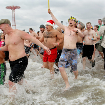 People run into the chilly water as they take part in the Coney Island Polar Bear Club's New Year's Day swim on January 1, 2013.