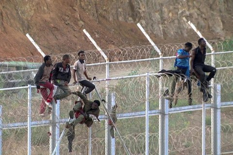 Hundreds of migrants claim 'victory' after storming border fence