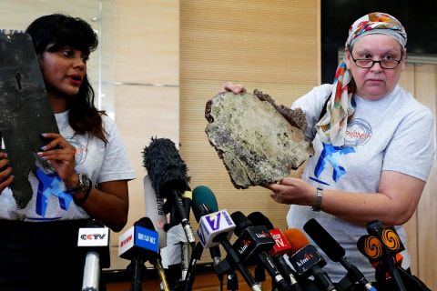 MH370 relatives show debris, ask authorities to do more