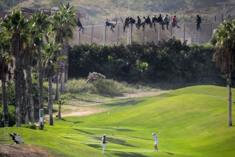 Golfers Play On as African Migrants Scale Spanish Border Fence