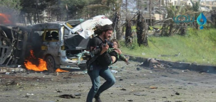 Image: Abd Alkader Habak helping a wounded Syrian boy and running to seek shelter