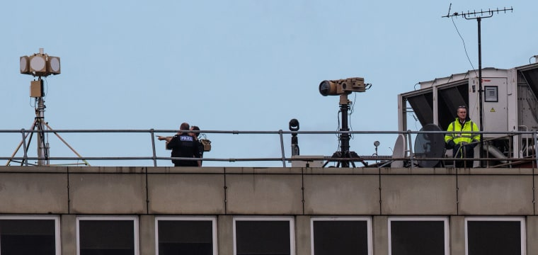 Image: Police officers and other people stand near equipment on the rooftop of a building as the runway is reopened at London Gatwick Airport