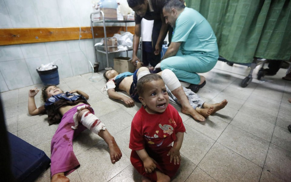 Image: Palestinian children, wounded in an Israeli strike on a compound housing a U.N. school in Beit Hanoun, in the northern Gaza Strip, cry as they lay on the floor at the emergency room of the Kamal Adwan hospital in Beit Lahiya, on July 24.