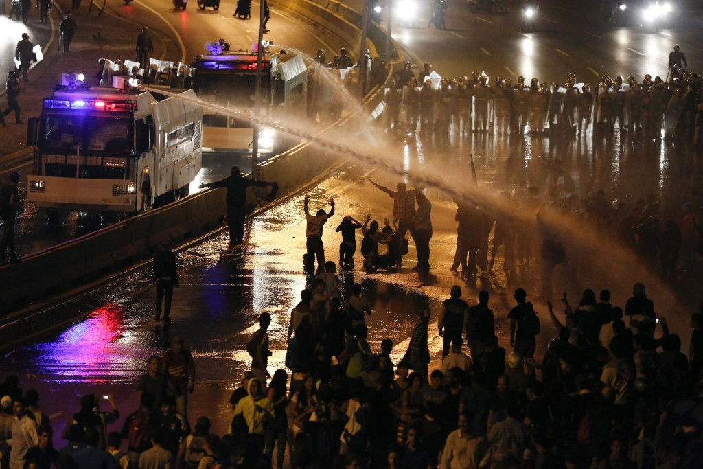 Image: Riot police use water to disperse opposition demonstrators as they block the city's main highway in Caracas