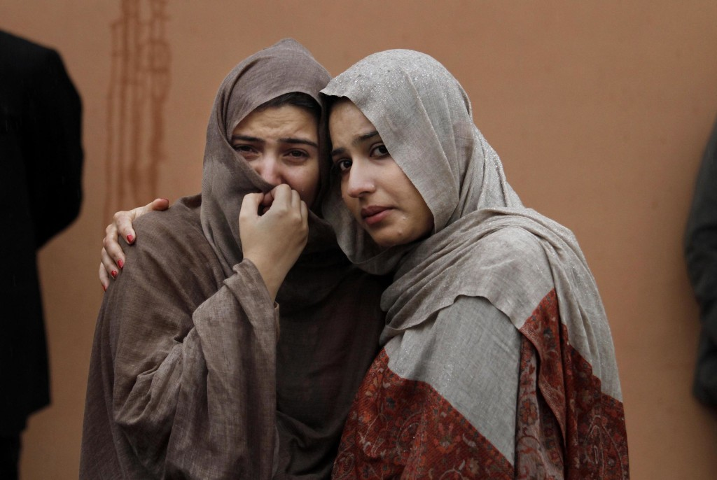 Image: Two women mourn outside a hospital morgue where the bodies of victims were brought.