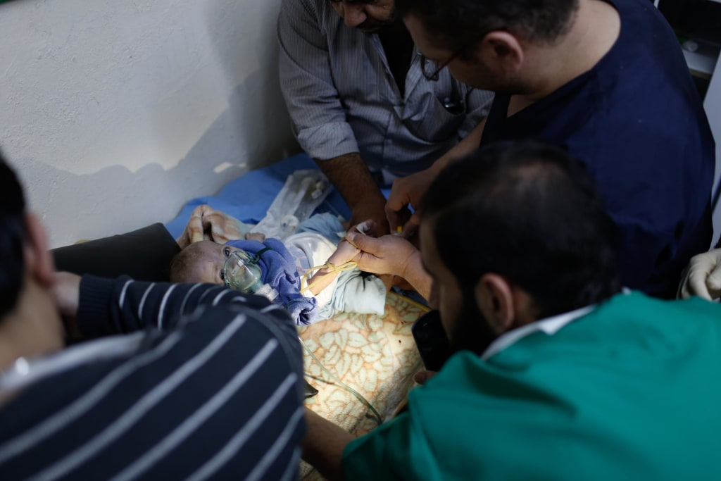 Image: A doctor uses an mobile phone to provide light during an operation on a baby suffering with Down's Syndrome