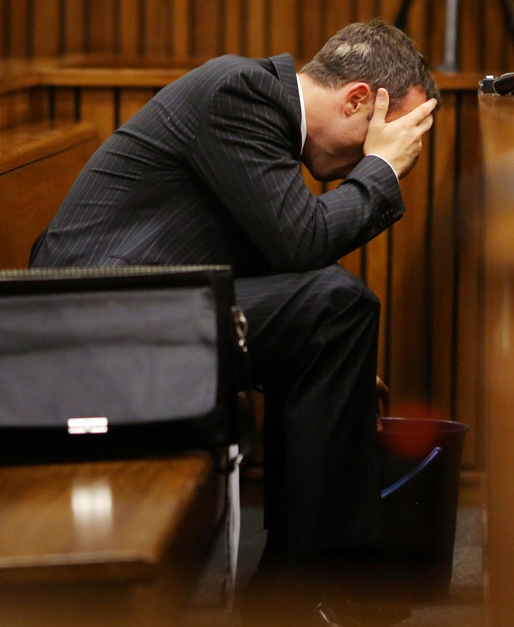 Image: Oscar Pistorius reaches for a bucket in the dock during his murder trial on Monday