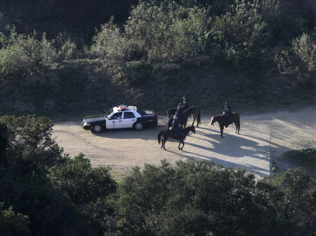 Image: LAPD mounted police officers search a hilly area below the iconic Hollywood sign in Los Angeles
