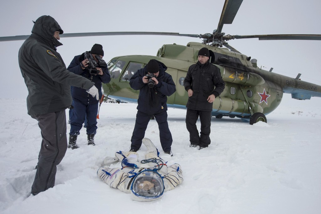 Image: A photographer and an operator document the suit worn by astronaut Hopkins from NASA after the landing of the Soyuz TMA-10M capsule in a remote area southeast of Zhezkazgan