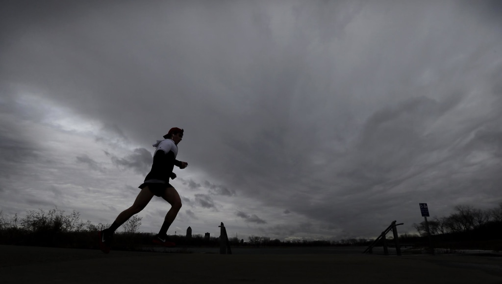 Image: A runner heads down the trail under cloudy skies at Greys Lake Park, on Tuesday, in Des Moines, Iowa.