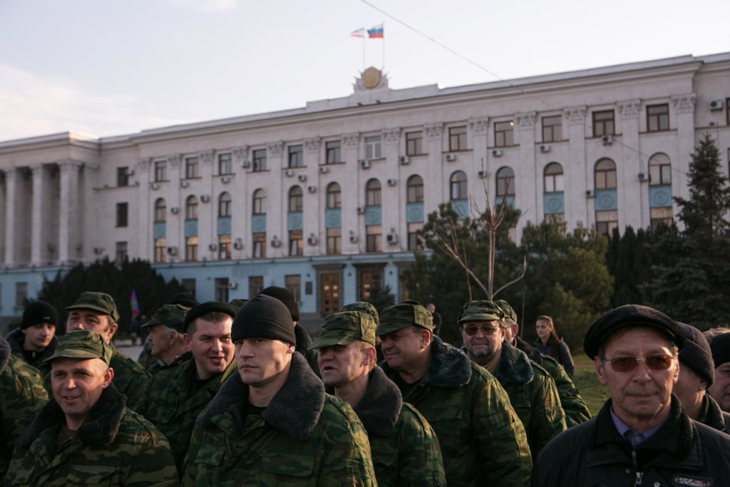 Pro-Russian volunteers gather in a square next to the Council of Ministers of Crimea's building, in Simferopol, two days ahead of the referendum over Crimea's bid to break away from Ukraine and join Russia.