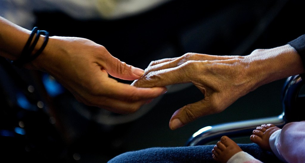 Guadalupe Tinajero, who has late stage Alzheimer's, reaches for her daughter, Cynthia Tinajero's hand.