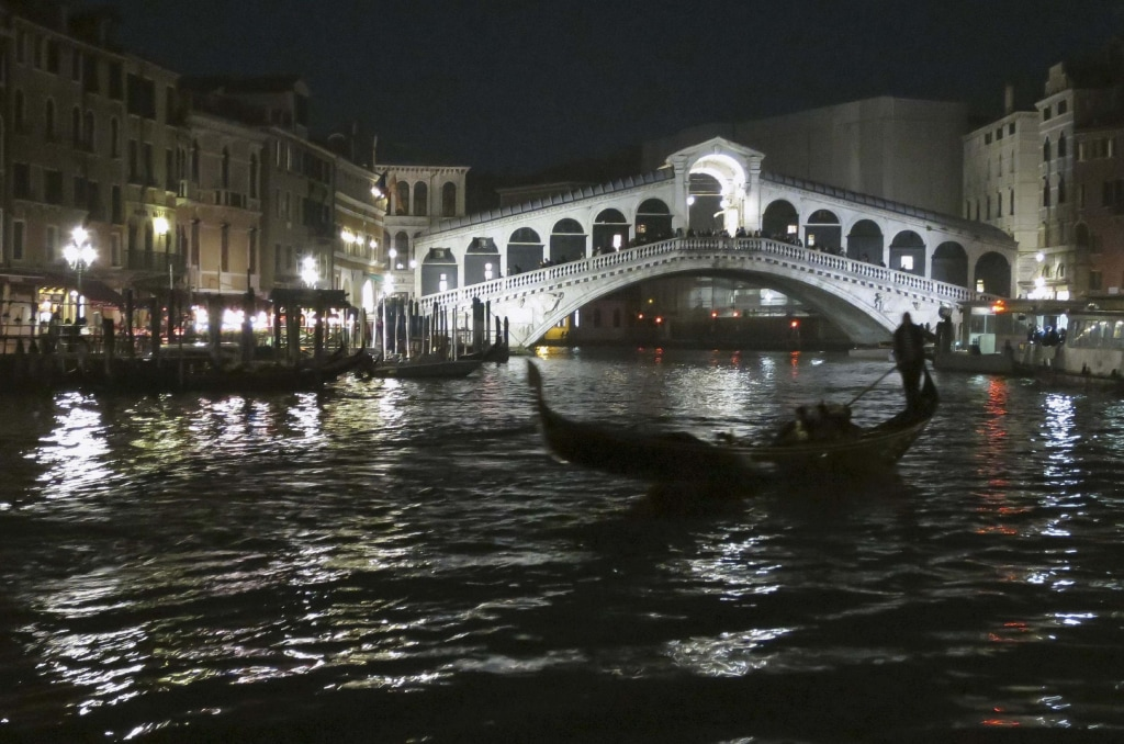 Image: A gondola passes along the Grand Canal in front of the Rialto bridge, in Venice