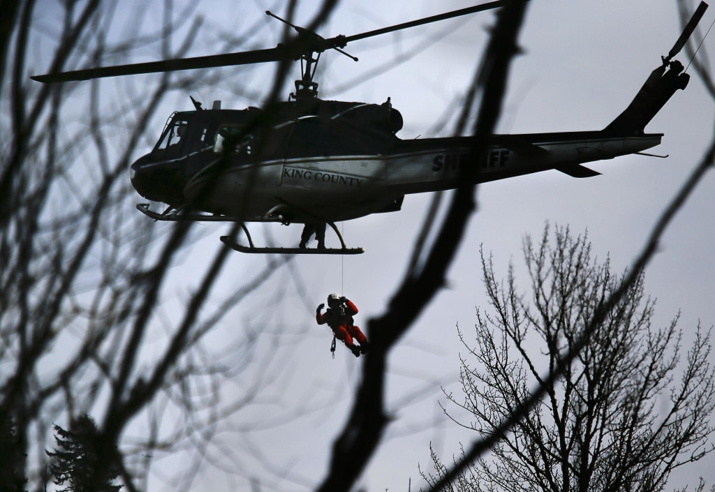 Image: A King County Sheriff helicopter lowers a rescuer