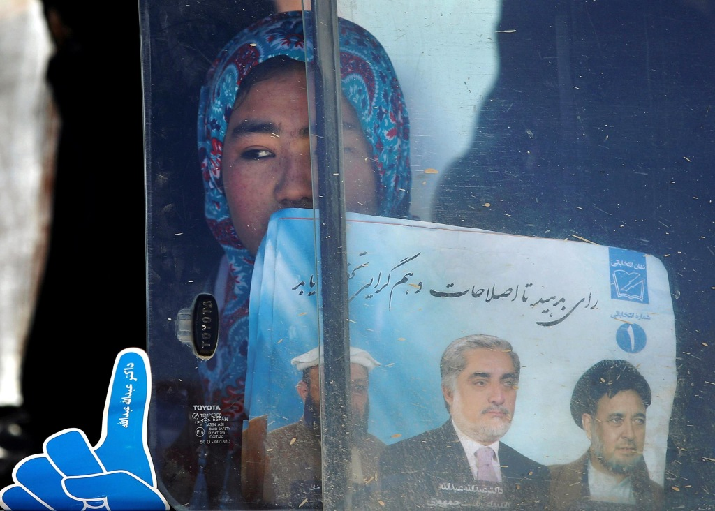 Image: A supporter of Afghan presidential candidate Abdullah looks out of a car window after an election rally in Mazar-I-Shariff