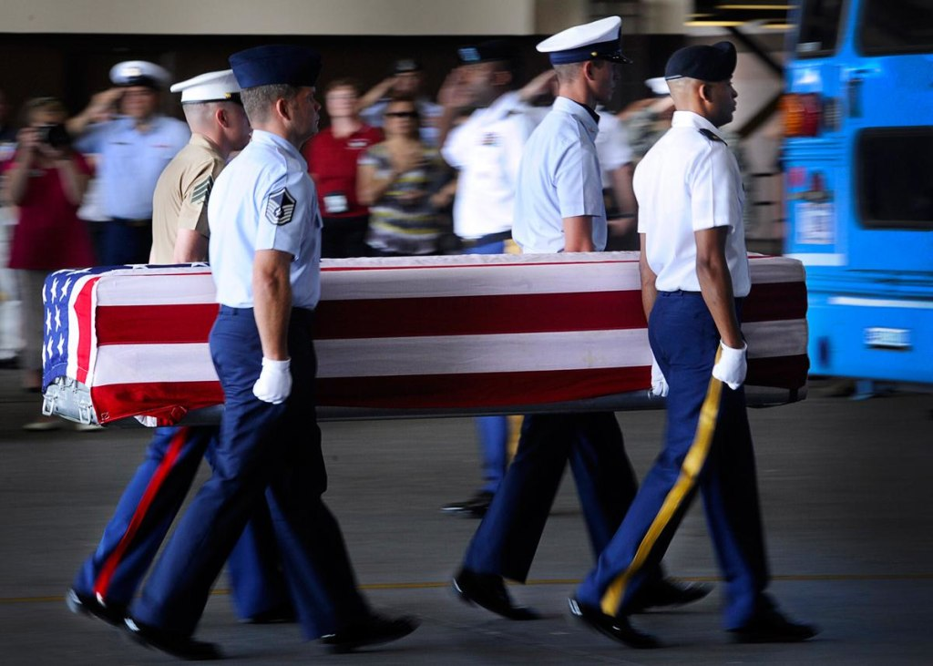 """Image: A joint service honor guard escorts a transfer case during an """"arrival ceremony"""" at Joint Base Pearl Harbor-Hickam in Honolulu on April 27, 2012."""