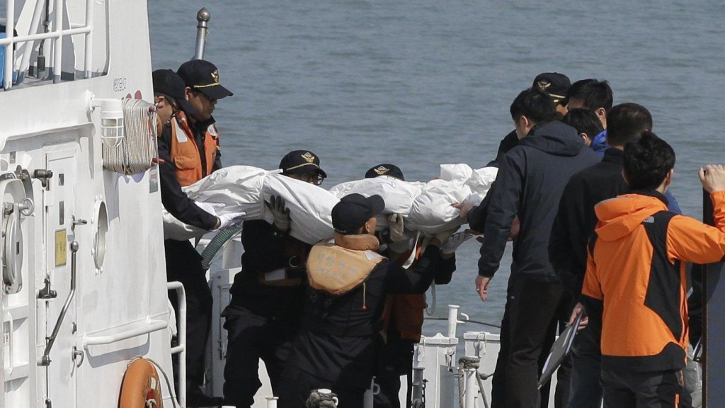 Image: Rescue workers bring the body of a passenger from the Sewol ferry to shore