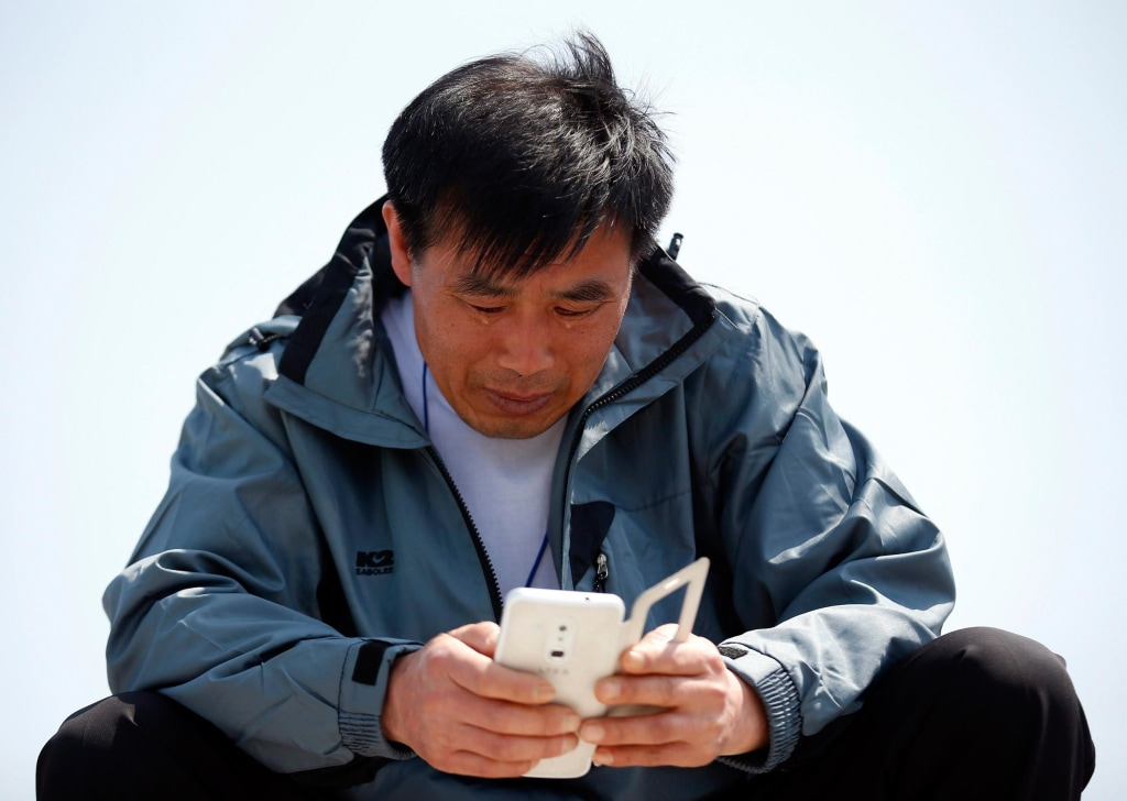 Image: Family member of a missing passenger onboard capsized Sewol ferry, cries while looking at a mobile device, at a port in Jindo