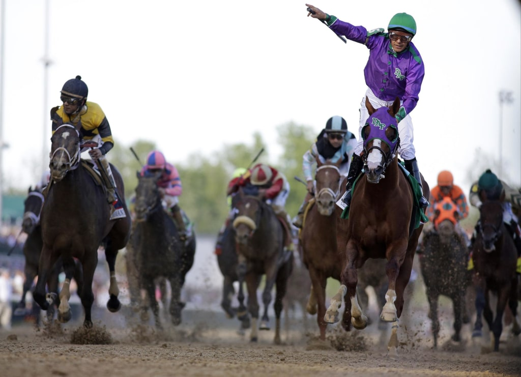 Image: Victor Espinoza rides California Chrome to a victory during the 140th running of the Kentucky Derby
