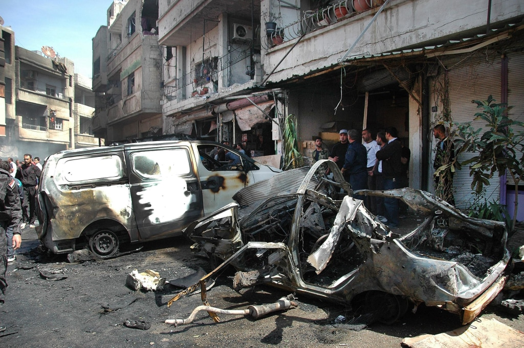 Image: Syrian policemen and citizens inspect the damage at the site of a car bomb explosion in the Abbasid neighborhood in Homs province on April 29.