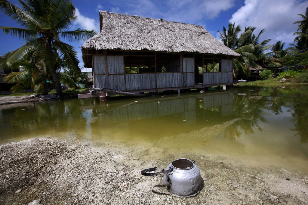 Image: An abandoned house that is affected by sea-water during high-tides stands next to a small lagoon near the village of Tangintebu on South Tarawa in the central Pacific island nation of Kiribati