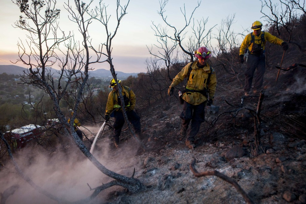 Image: Fire crew put out smouldering embers from the Cocos Fire in San Marcos