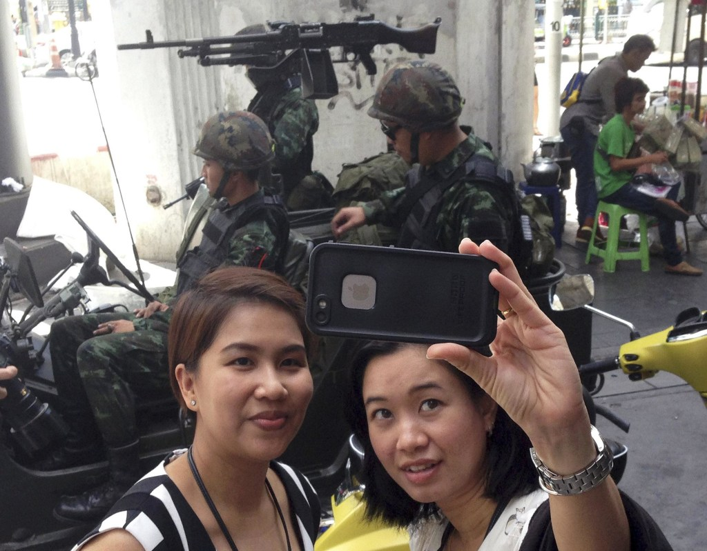 Image: Residents stop to take a photograph of themselves at a military checkpoint in central Bangkok