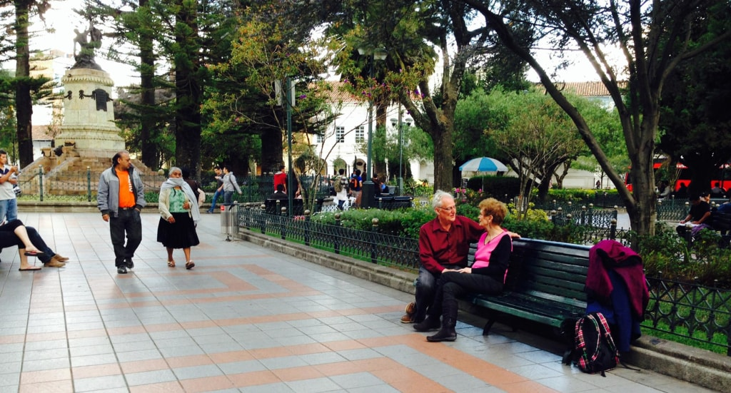 An American couple sits on a park bench in Ecuador.