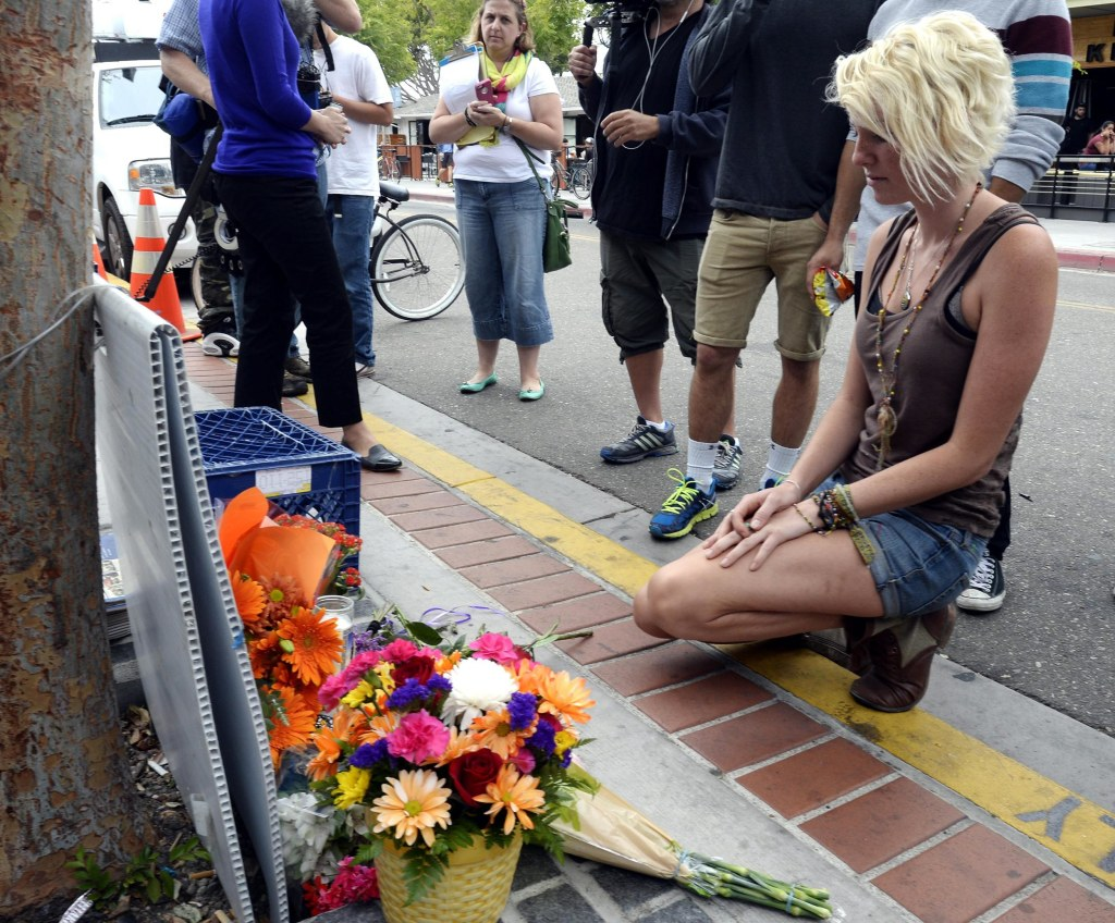 Image: A woman kneels in front of a makeshift memorial for victims of a deadly shooting in Isla Vista.