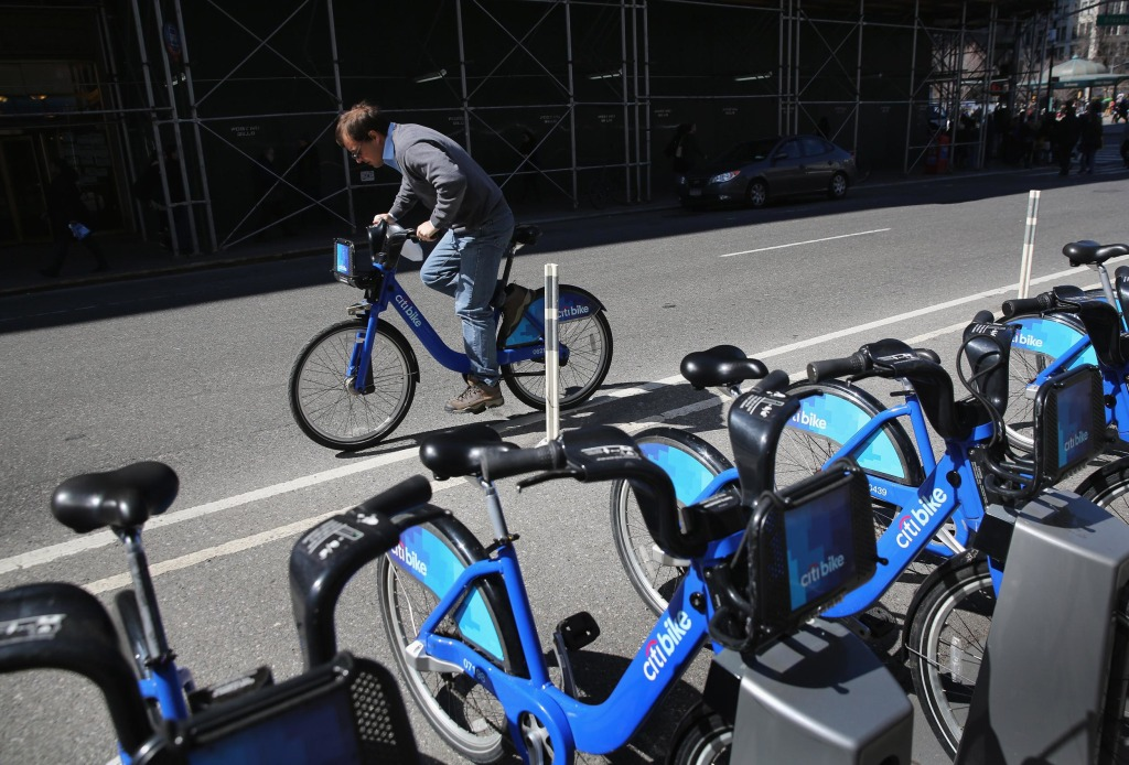 Image: A Citi Bike user pedals off from a bicycle station