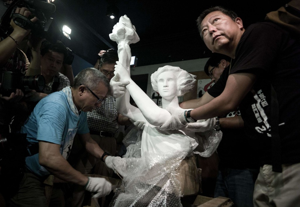 """Image: A """"statue of democracy"""" is unpacked by Lee Cheuk-yan, right, at the  June 4 Memorial museum in Hong Kong"""