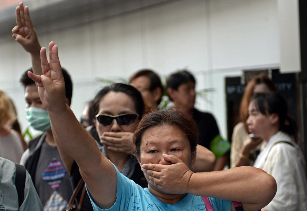 Image: Anti-coup protesters flash a three-finger salute