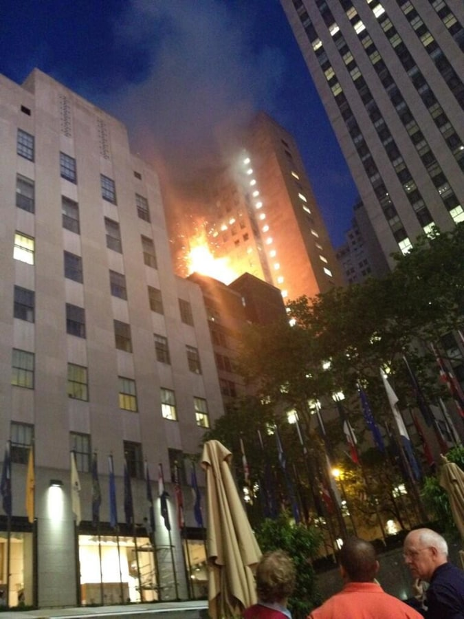 Image: Heavy smoke and flames are seen shooting from the top of a building on Fifth Avenue across from Rock Center
