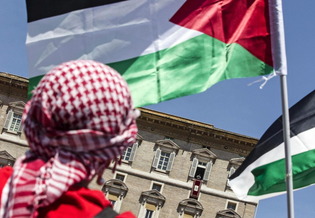 Image: A man waves Palestinian flags as Pope Francis holds the Regina Coeli prayer in Saint Peter's Square