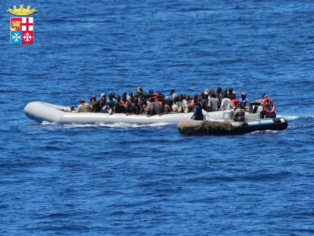 Image: Migrants on boats being intercepted by the Italian army off the coast of Sicily on June 6, 2014.