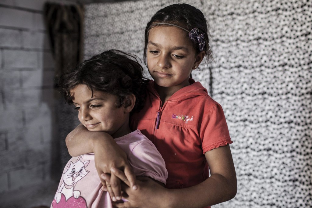 Image: Najua and her younger sister Iman, 6, stand in the tiny shop front room where they live with their mother Meyada and two brothers in Reyhanli, Turkey.