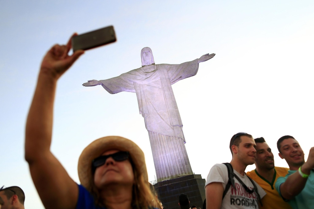 Image: A woman poses for a selfie in front of the statue of Christ the Redeemer in Rio de Janeiro