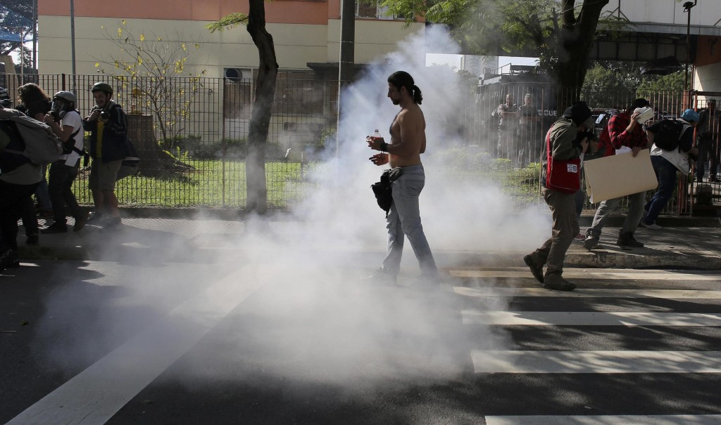 Image: Demostrator walks near to tear gas fired by mlitary police at demostrators during protest against 2014 World Cup in Sao Paulo