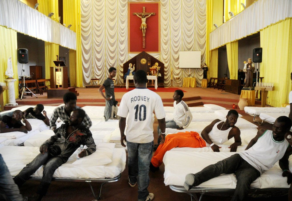 Image: Migrants from Africa are temporarily sheltered in the Catholic church of  St. Curato D'Ars in Palermo, Sicily
