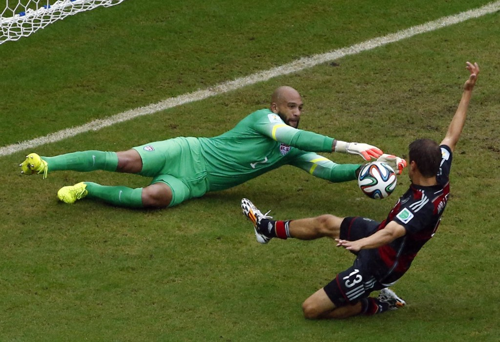 Germany's Mueller challenges goalkeeper Howard of the U.S. during their 2014 World Cup Group G soccer match at the Pernambuco arena in Recife