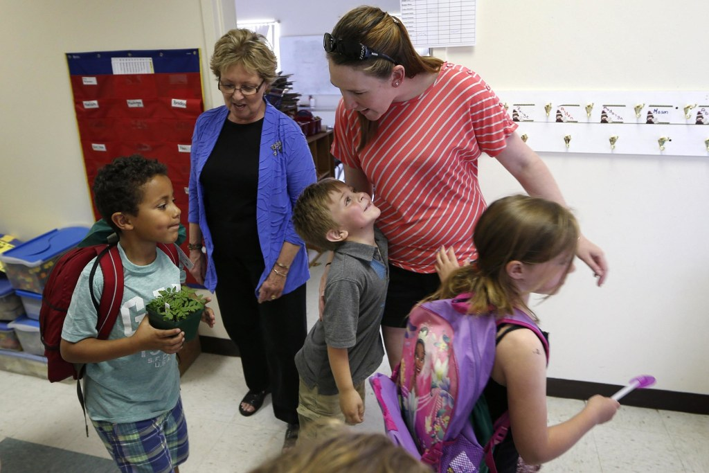 Image: Kindergartner Russell Emery, center, gives a hug to teacher's assistant Ashley Porter on the final day of school at the Wellington public school in Monticello, Maine